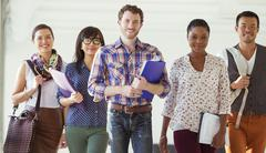 Portrait of confident creative business people walking in office corridor - stock photo