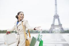 Woman carrying shopping bags by Eiffel Tower, Paris, France Stock Photos