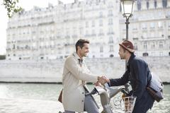 Businessmen handshaking on bicycles along Seine River, Paris, France - stock photo