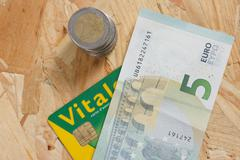 Concept of expensive healthcare with coins,notes and french health card Kuvituskuvat