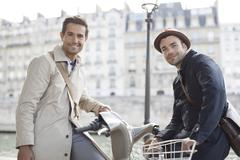 Businessmen on bicycles along Seine River, Paris, France - stock photo