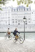 Men riding bicycles along Seine River, Paris, France - stock photo