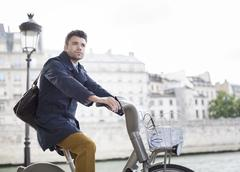 Businessman riding bicycle along Seine River, Paris, France Stock Photos