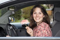 young woman sitting in a car and holding a flower - stock photo