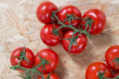 Stock Photo of Fresh  tomatoes on a cluster over wooden  table