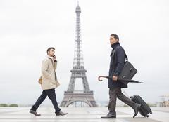 Businessmen walking past Eiffel Tower, Paris, France - stock photo