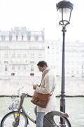 Businessman using cell phone on bicycle along Seine River, Paris, France - stock photo