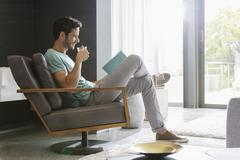 Man drinking tea and reading book in living room Stock Photos