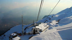 View from cableway cabin lifting skiers to snowy mountain pick - stock footage