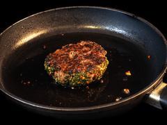 Frying seasoned hamburger in fry pan - stock photo