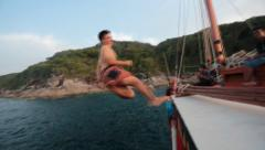 Man jumping off boat into ocean slow motion Stock Footage