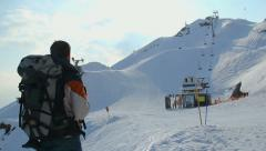 Tourist with backpack looking at snowy skiing run on mountains Stock Footage