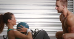 Woman doing sit ups with trainer at crossfit gym Stock Footage