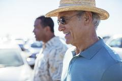 Senior men in sunny parking lot - stock photo