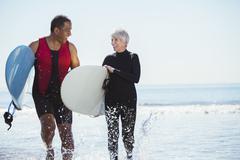 Senior couple with surfboards on beach Kuvituskuvat
