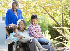 Grandparents and grandchildren in garden Stock Photos