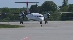 Airplane Bombardier DHC-8-402 Q400 taxiing to the gate after landing at Stock Footage