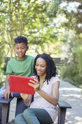 Mother and son using digital tablet outdoors Stock Photos