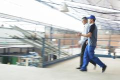 Supervisor and worker walking in food processing plant Stock Photos