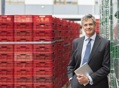 Portrait of confident supervisor with digital tablet in food processing plant Stock Photos