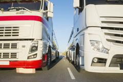 Commercial trucks side by side on the road Stock Photos