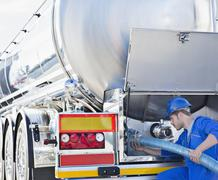 Worker attaching hose to back of stainless steel milk tanker - stock photo