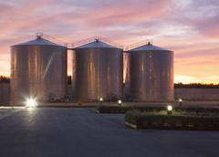 Silage storage towers against dramatic sky - stock photo