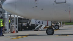 Ground crew bringing wheel chocks for the parked Boeing 737 at the gate at Stock Footage