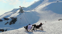 Two relaxed men sitting in chairs, observing snowy skiing run Stock Footage