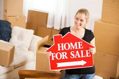 Moving: Woman Holds Sale Sign Amidst Stacks Of Boxes - stock photo