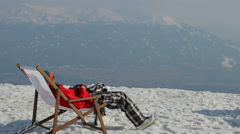 Snowboarder having rest in chair with gadget on top of mountain Stock Footage