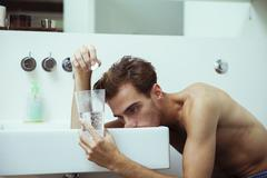 Hungover man watching effervescent tablets in bathroom Stock Photos