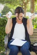Upset Young Woman with Pencil and Crumpled Paper in Hands - stock photo