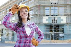 Young Attractive Female Construction Worker Wearing Hard Hat and Gloves - stock photo