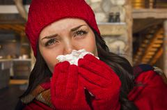Stock Photo of Miserable Sick Woman Inside Log Cabin Blowing Her Sore Nose With Tissue.
