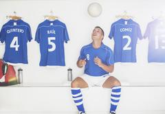 Soccer player bouncing ball in locker room - stock photo