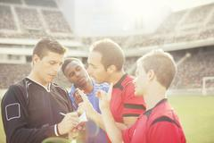 Soccer players arguing with referee on field Stock Photos