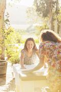 Mother and daughter laying table cloth on table - stock photo