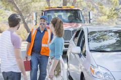 Roadside mechanic arriving to help couple - stock photo