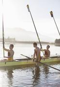 Rowing team lifting oars in lake - stock photo