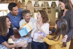 Older woman being given gift by family Stock Photos