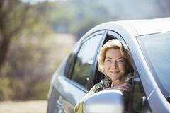 Portrait of confident senior woman leaning out car window Stock Photos