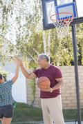 Stock Photo of Grandfather and granddaughter high fiving at basketball hoop