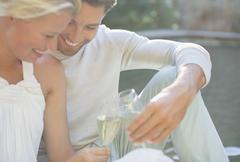 Couple toasting each other with champagne outdoors - stock photo