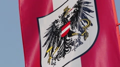 Austrian flag with coat of arms, national emblem waving in sky Stock Footage