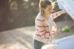 Woman checking oil under automobile hood at roadside - stock photo