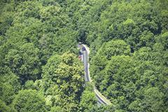 Aerial view of winding road through forest. Kuvituskuvat