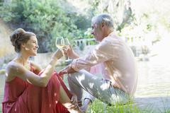 Couple toasting each other outdoors - stock photo