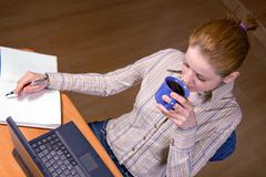 woman drinking from a cup and write in the workbook with work on a laptop - stock photo