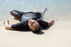 Tired man lying on the beach - stock photo